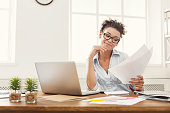 Paperwork. Smiling business woman in formal wear sitting at wooden desk in modern office, reading report document, side view, copy space