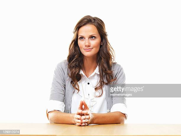 Smiling business woman sitting at table with hands clasped