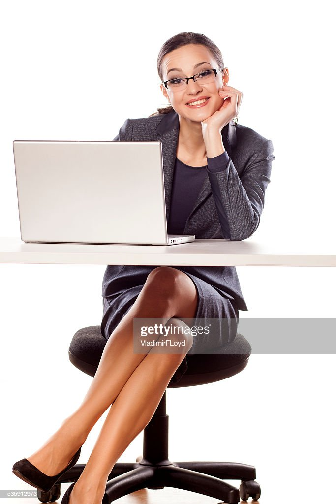 Smiling business woman sitting at the table with laptop : Stock Photo