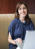Smiling business woman with computer in restaurant