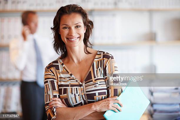 Smiling business woman with male colleague in the background