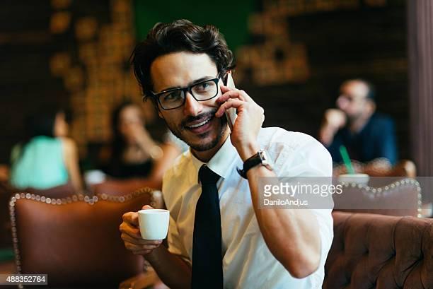 Uomo d'affari sorridente relax godendo il suo caffè