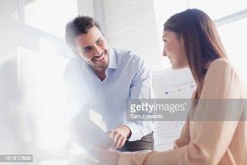 Smiling businessman and businesswoman in conference room