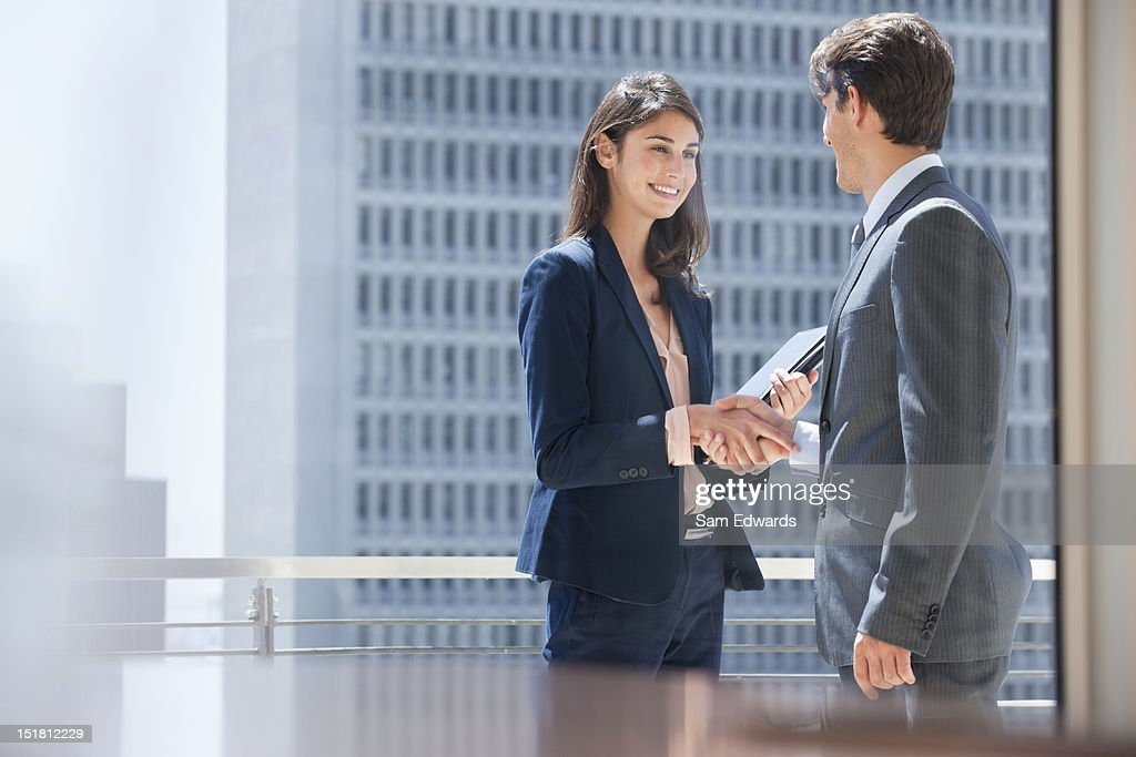 Smiling businessman and businesswoman shaking hands on urban balcony : Stock Photo