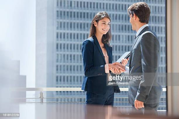 Smiling businessman and businesswoman shaking hands on urban balcony