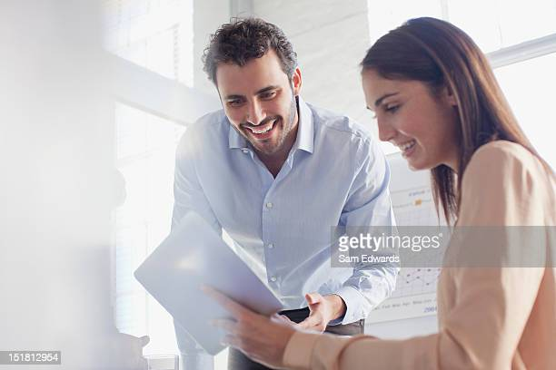 Smiling businessman and businesswoman using digital tablet in office