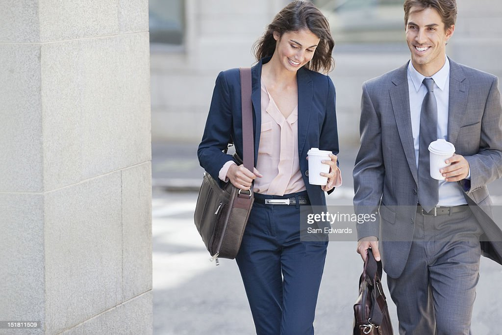 Smiling businessman and businesswoman walking with coffee cups : Stock Photo