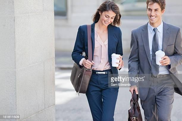 笑顔のビジネスマンやビジネスウーマンのウォーキング、コーヒーカップ