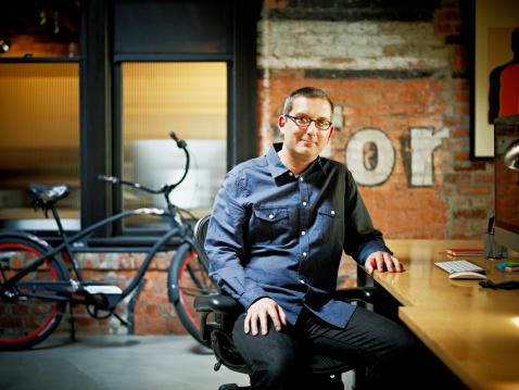 Smiling businessman at desk in startup office