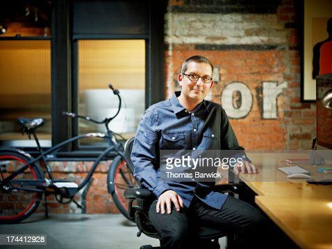 Smiling businessman at desk in startup office