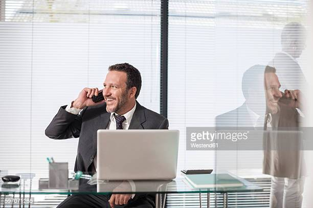 Smiling businessman at desk with laptop and telephone