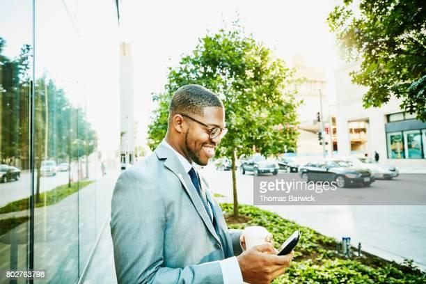 Smiling businessman checking smartphone on city sidewalk