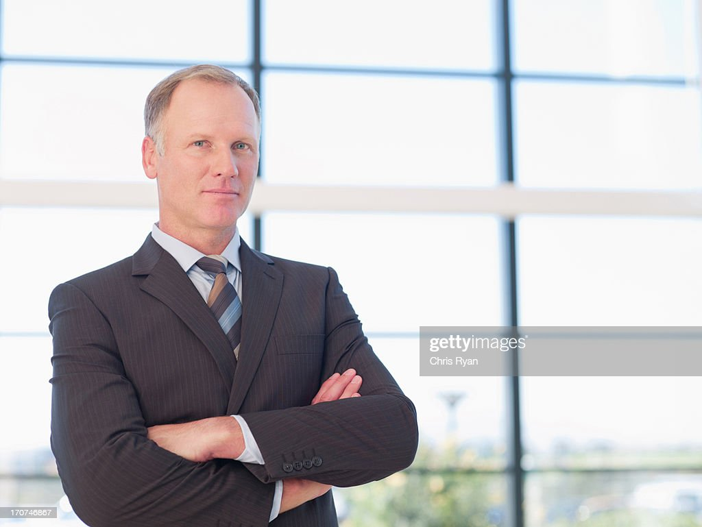 smiling businessman closing arms : Stock Photo