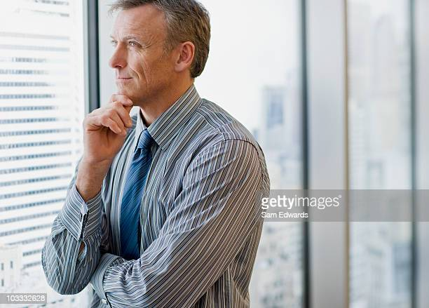 Smiling businessman daydreaming and looking out office window