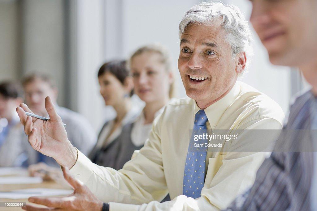 Smiling businessman gesturing in meeting : Stock Photo