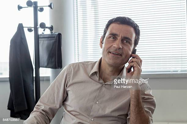 Smiling businessman having phone call in office