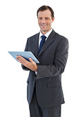 Smiling businessman holding a tablet computer on white background