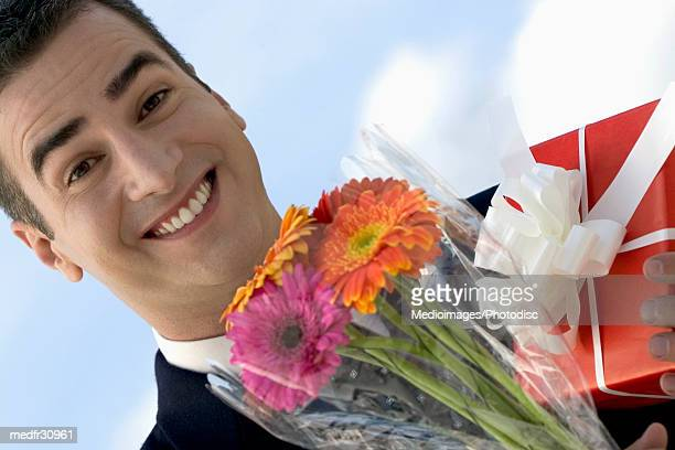 Smiling businessman holding bouquet of flowers and gift wrapped in red paper outdoors, close-up