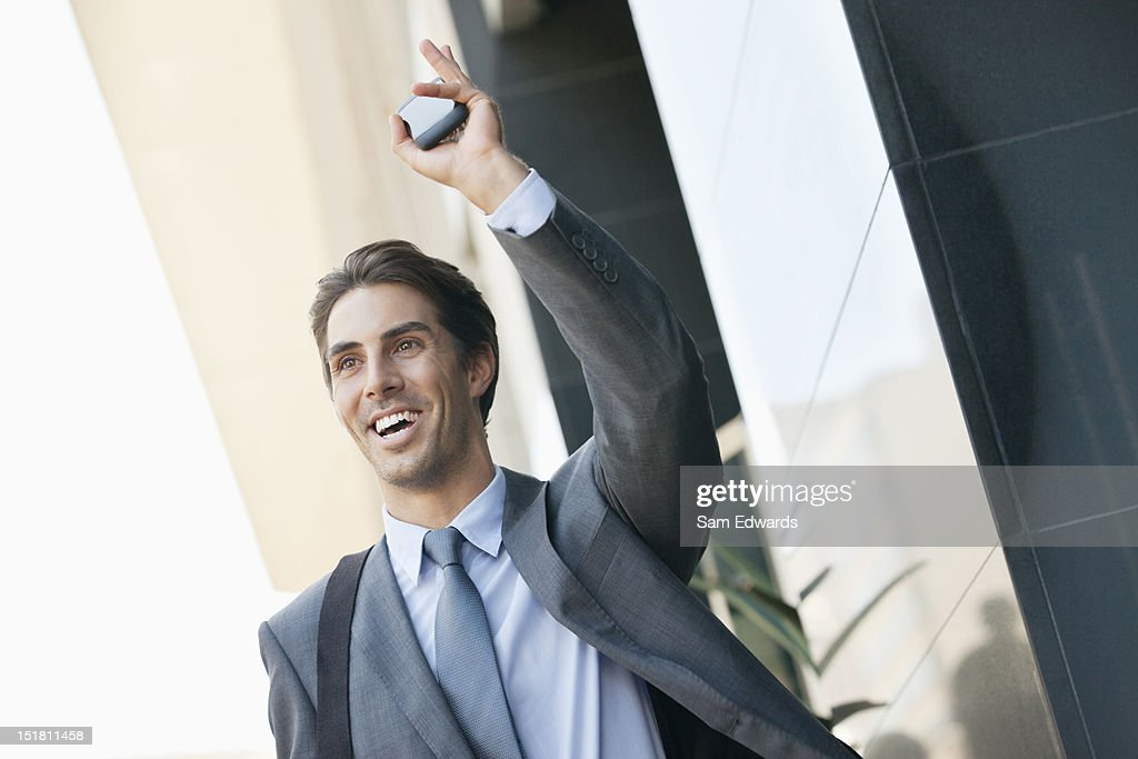 Smiling businessman holding cell phone and waving : Stock Photo