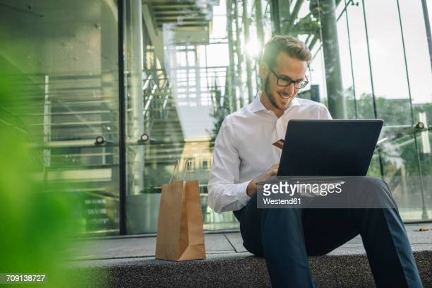 Smiling businessman holding credit card and using laptop in lobby