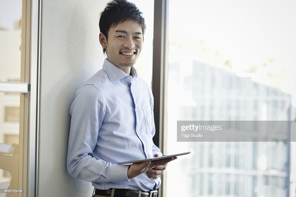 Smiling businessman holding digital tablet