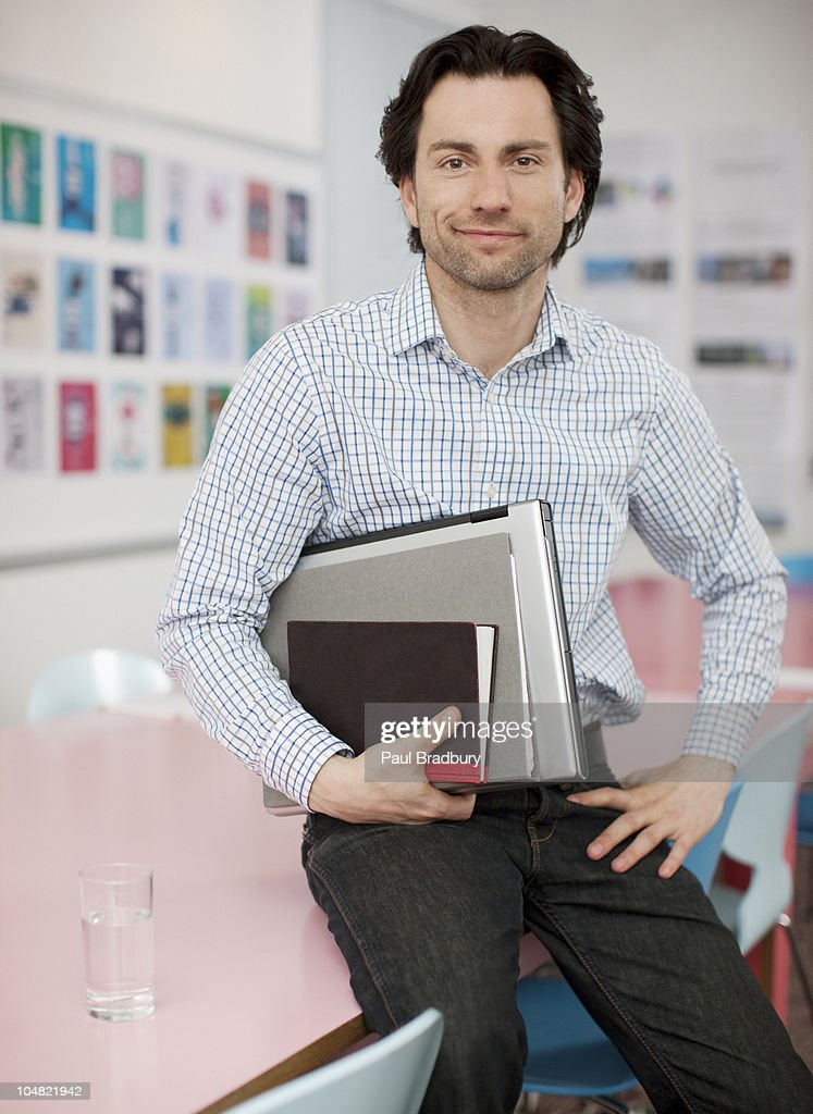 Smiling businessman holding laptop and books in office : Stock Photo
