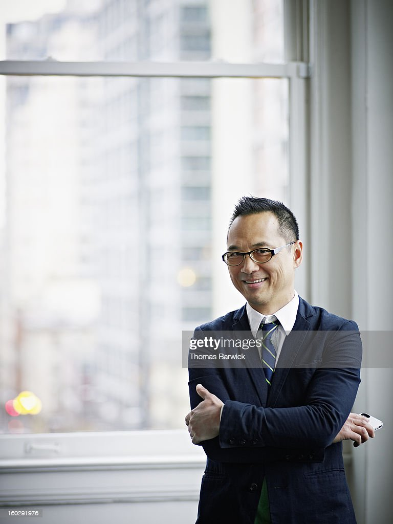 Smiling businessman holding smartphone in office : Stock Photo