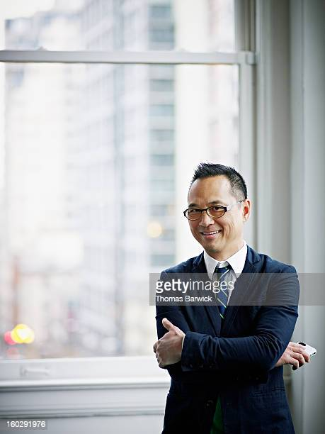 Smiling businessman holding smartphone in office