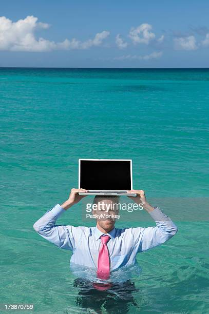 Smiling Businessman Holds Laptop on Head in Sea