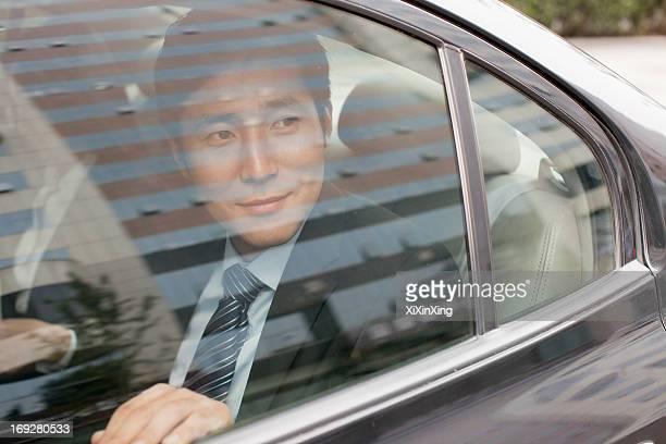 Smiling Businessman in Car Back
