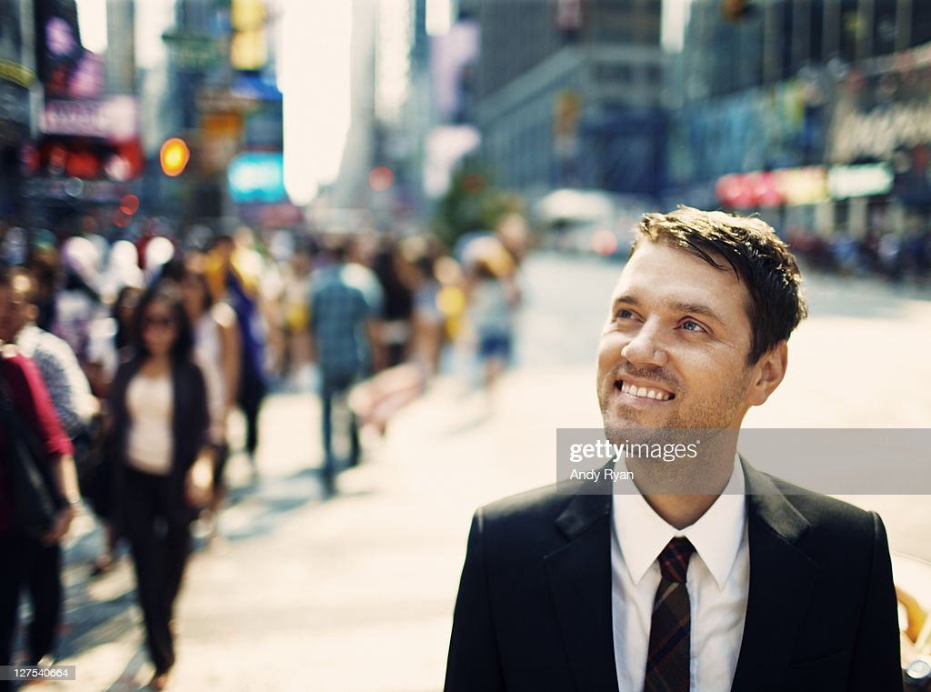 Smiling businessman in city, looking up.