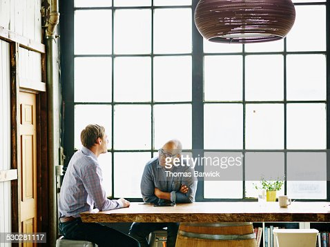 Smiling businessman in discussion with colleague