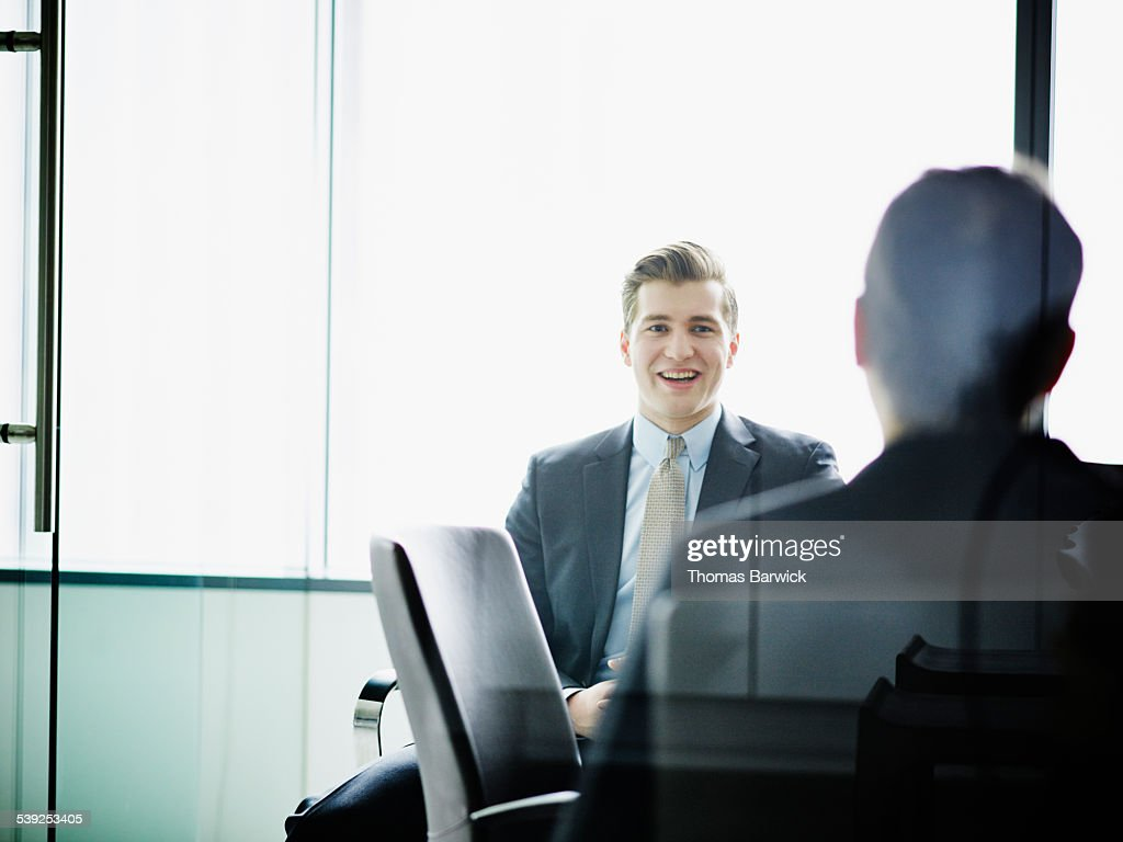 Smiling businessman in discussion with colleague : Stock Photo