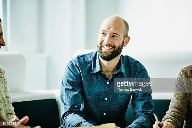 Smiling businessman in discussion with colleagues