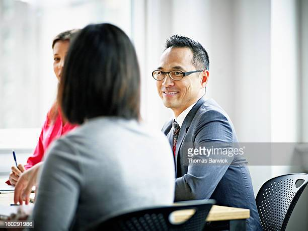Smiling businessman in discussion with coworkers
