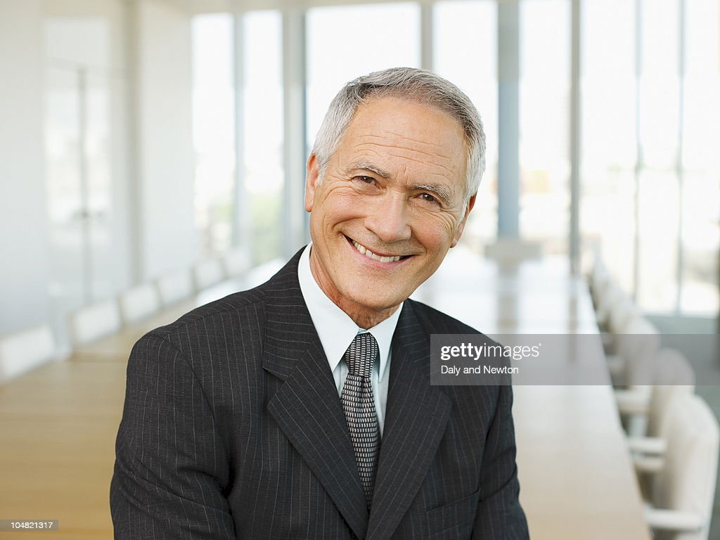 Smiling businessman in empty conference room