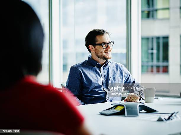 Smiling businessman in meeting with coworkers