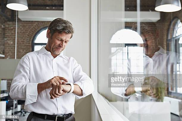 Smiling businessman in office looking at smartwatch
