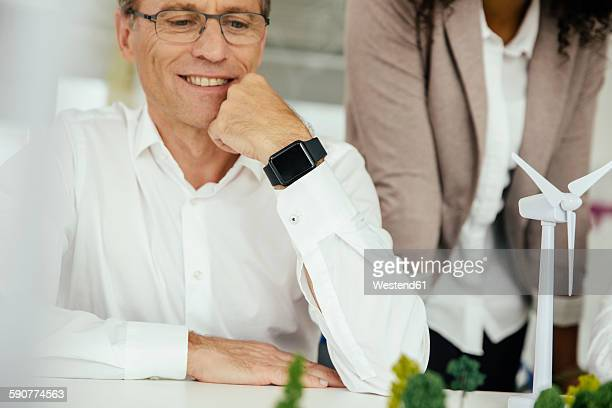Smiling businessman in office with wind turbine model