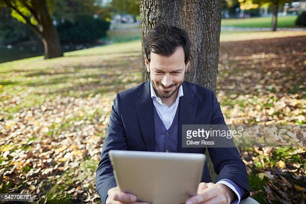 Smiling businessman in park using digital tablet