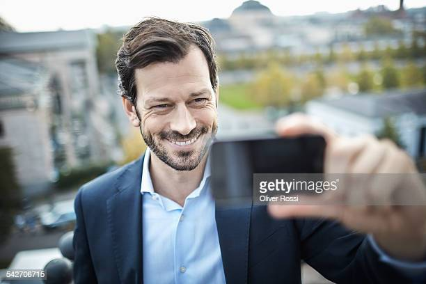 Smiling businessman in the city taking a selfie