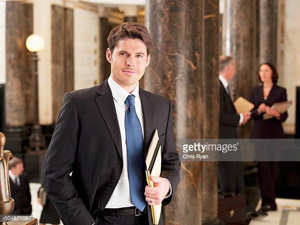 Smiling businessman leaning against pillar in corridor