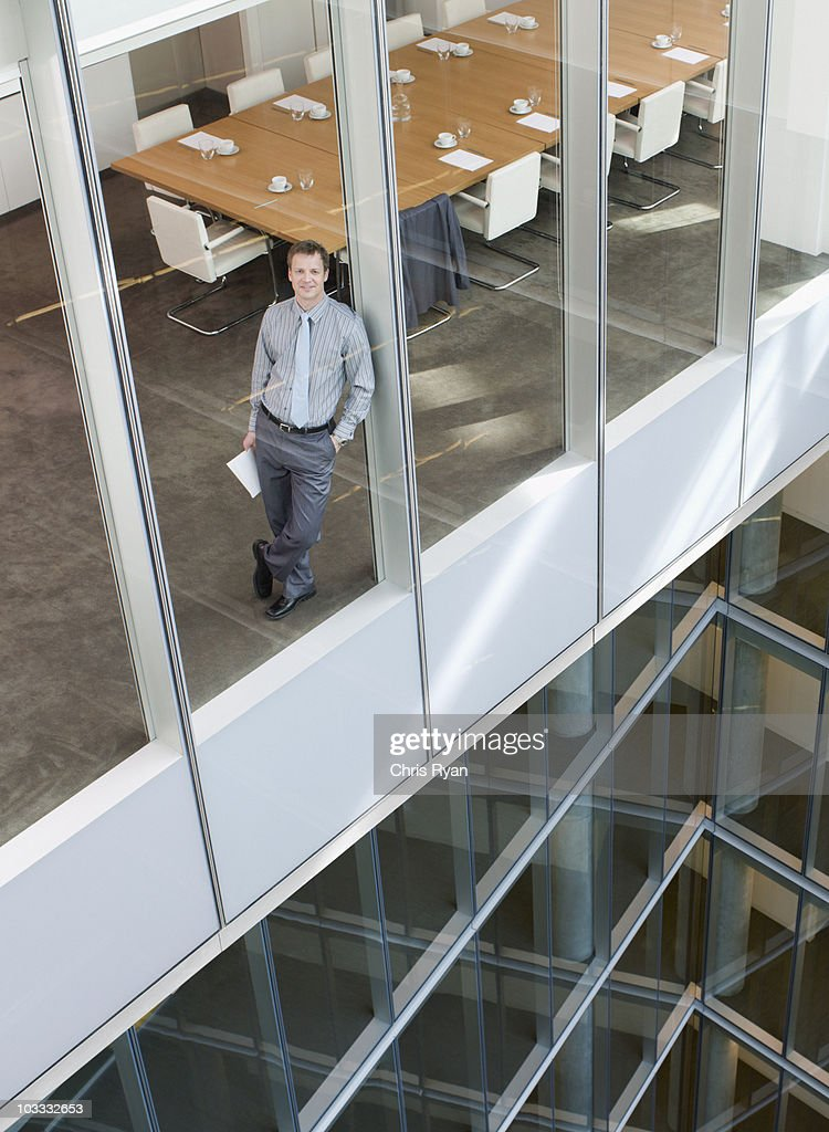 Smiling businessman leaning against window in conference room : Stock Photo
