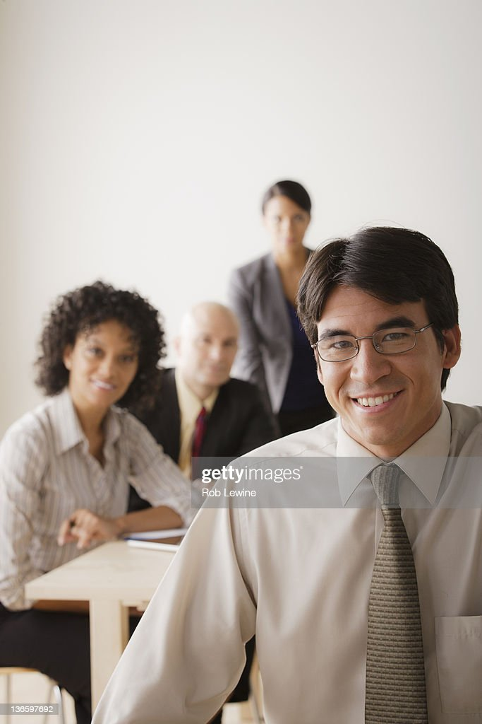 Smiling businessman looking at camera, business team in background : Stock Photo