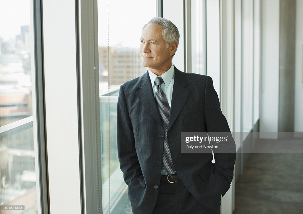Smiling businessman looking out office window