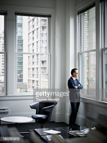 Smiling businessman looking out office window : ストックフォト