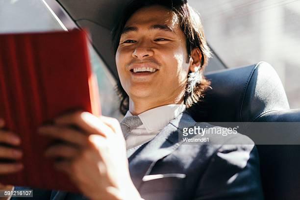 Smiling businessman on back seat of car using digital tablet