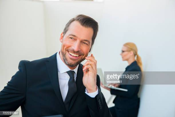 Smiling businessman on cell phone and businesswoman using laptop outdoors