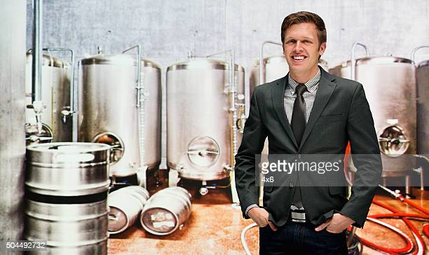 Smiling businessman on mobile at a brewery