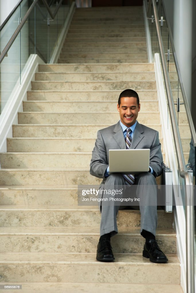 Smiling businessman on steps with laptop : Stock Photo